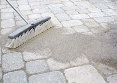 Broom Sweeping Sand into Pavers